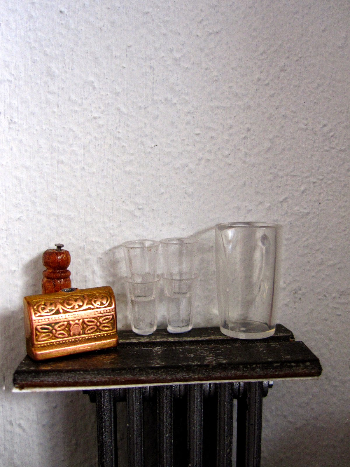 Modern dolls' house miniature cafe water shelf with jug and glasses, pepper grinder and sugar bowl in the shape of a treasure chest.