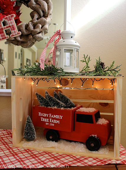 A made over red vintage truck with Christmas trees in a crate is the star of this wintery entryway table
