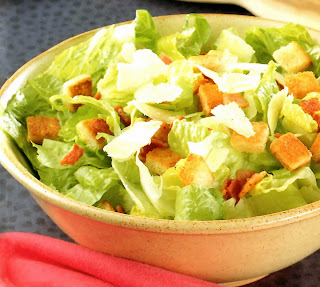 Caesar Salad: Classic Caesar salad served in a cream bowl