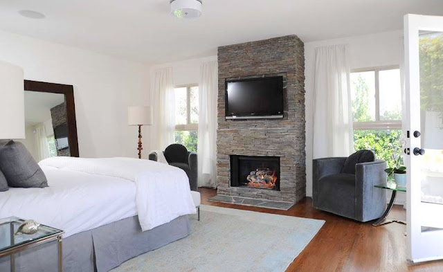 Master bedroom with a stone fireplace with a wall mounted flat screen TV, on each side of the fireplace is a grey armchair in front of a window with floor length white curtains, the room has wood floors, a grey area rug and a large mirror leans up against the wall. French doors lead outside.