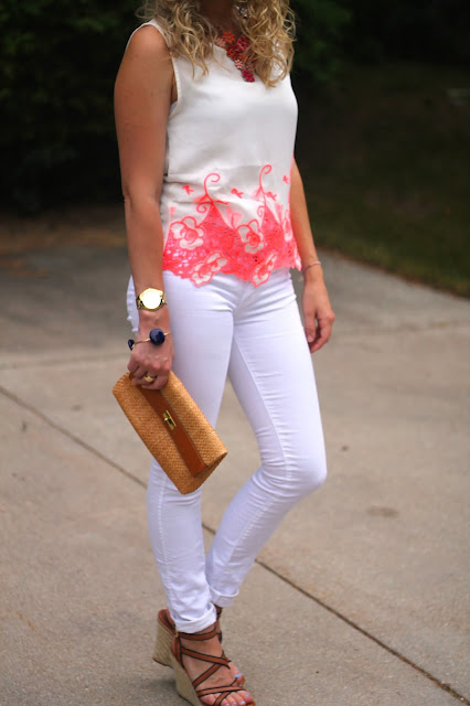 white jeans, white top with neon orange detail, straw clutch, wedges