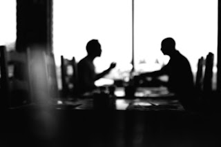 Two people converse at a cafe in silhouette.