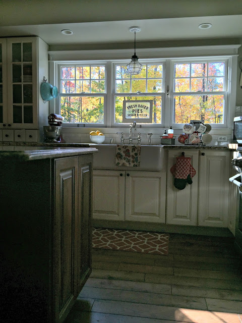 Fall foliage outside triple kitchen window over sink with farmhouse sink and caged pendant - www.goldenboysandme.com