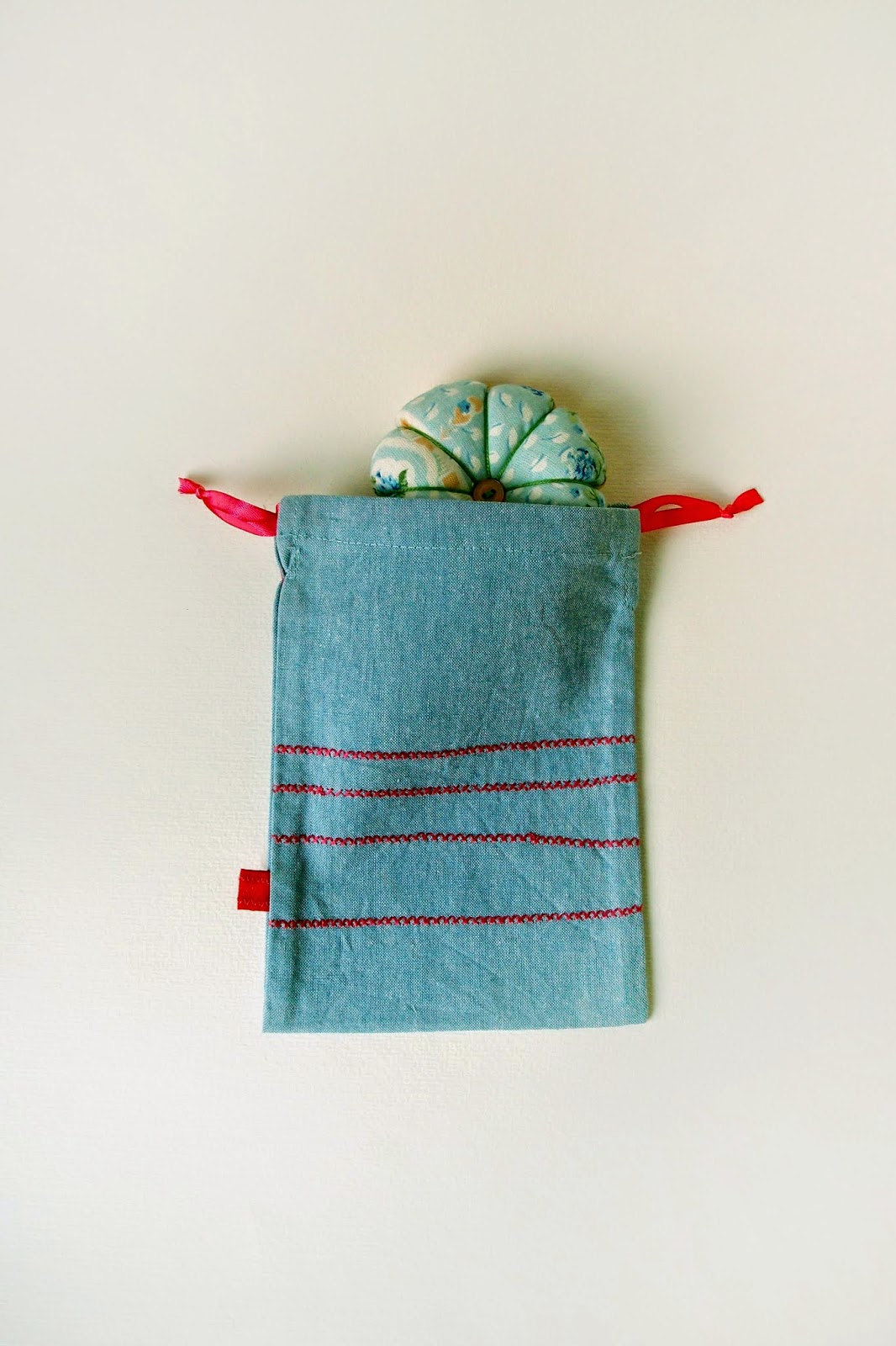 mini drawstring cotton denim bag with fuchsia cross stitch embroidery