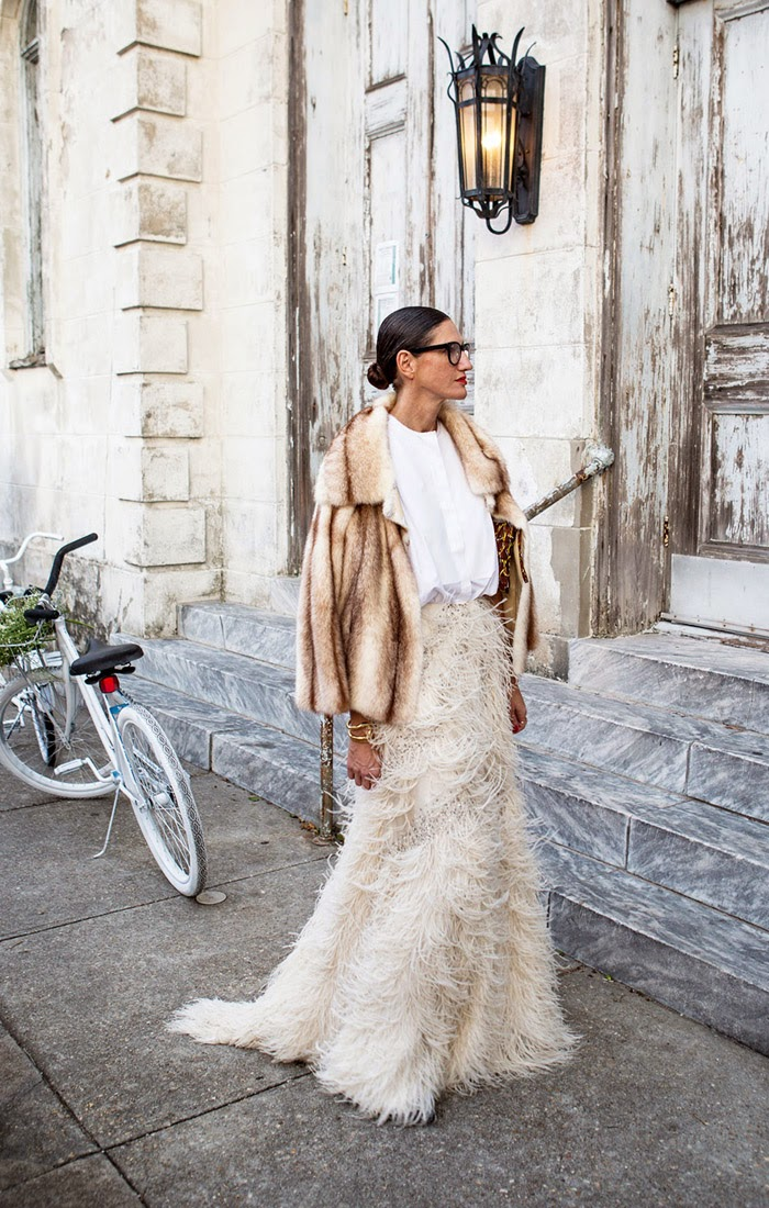 Jenna Lyons, the creative director and president of J.Crew stands outside the wedding of Beyonce's sister Solange Knowles in an all white ensemble besides a cycle and flowers