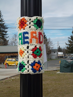 "Yarnbombing tag: granny squares with panel that says ""READ"""