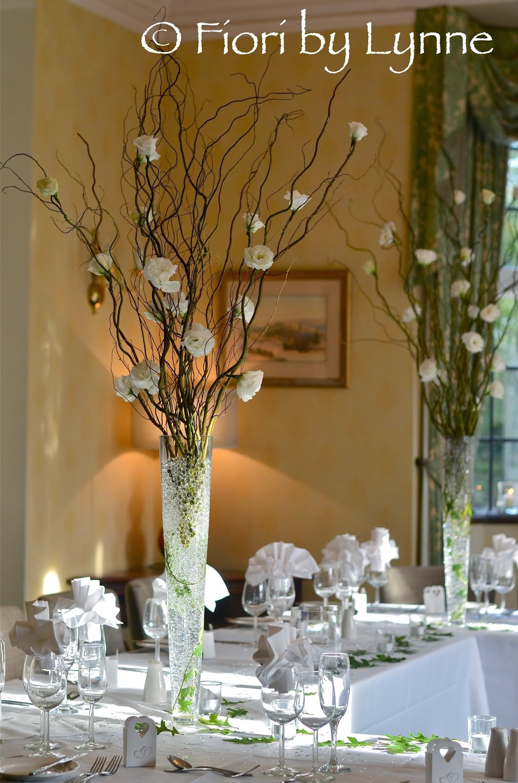 Wedding flowers blog 2014 tall vase of curly twigs and lisianthus flowers the table below is decorated with massed tea lights and scattered oak leaves to create a wonderfully reviewsmspy