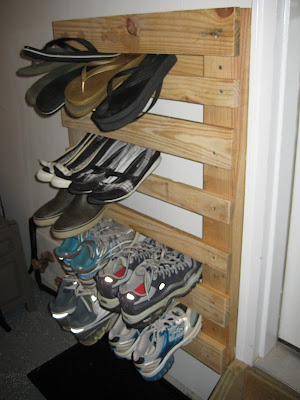 wooden pallet hanging on wall used as shoe storage