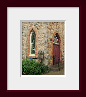 A gothic stone church with spring flowers blooming under the arched stained glass window
