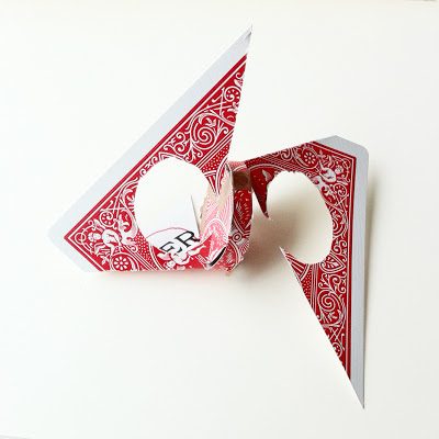 A red backed playing card which has been folded and cut into an abstract construction.