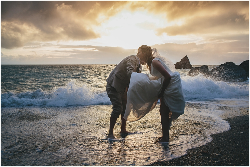 Bride and groom laughing on the beach with bare feet