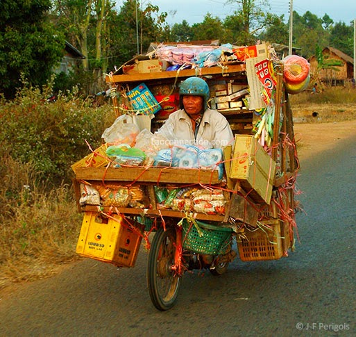 Lao travelling salesman with wares packed on his motorbike