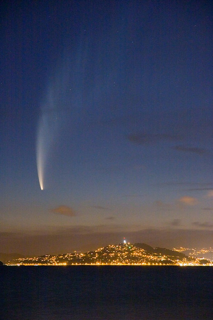 A white, long-tailed comet in the sky over a lit city