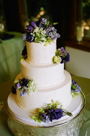 Topped with bouquetcoordinating flowers of green and purple