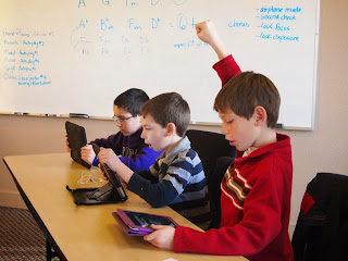 Elementary students excitedly use iPads in the classroom