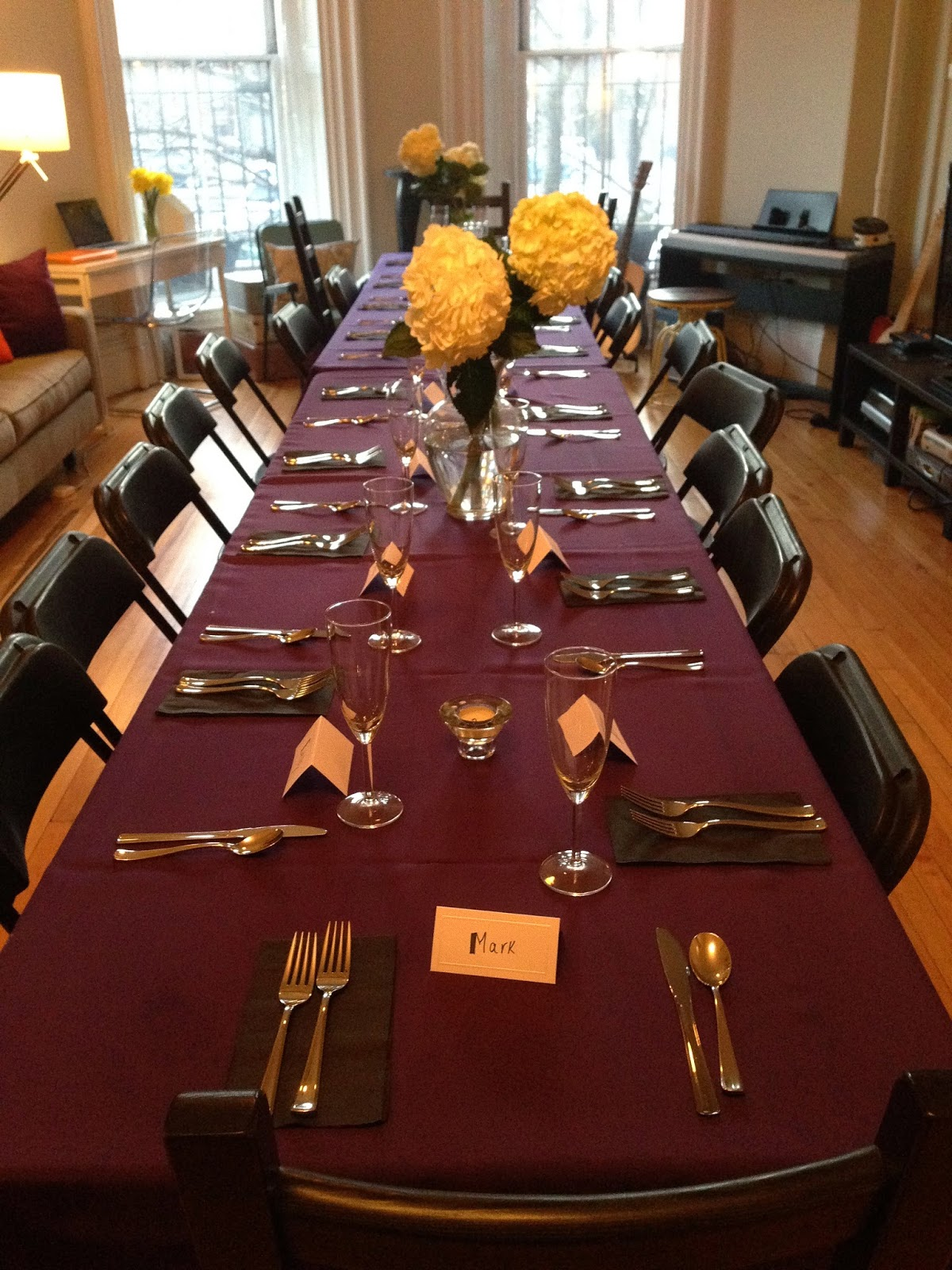 Table set for 18, purple linens and black chairs.