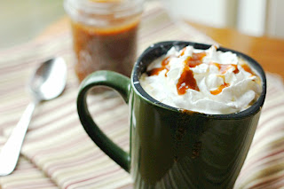 pumpkin caramel hot apple cider in a green mug with caramel sauce in the background