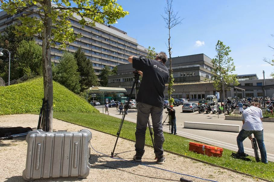 Media stand in front of the Lausanne University Hospital (the ''CHUV'') in Lausanne, Switzerland, Monday, June 16, 2014. Former German Formula One driver Michael Schumacher is no longer in a coma and has left a French hospital where he had been receiving treatment since a skiing accident in December, but has been transferred to the Lausanne University Hospital his manager said Monday, June 16 2014.