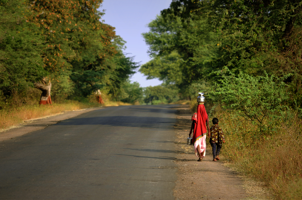 Woman and child are walking in the countryside of India