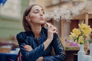 A woman is smoking e-cigarette