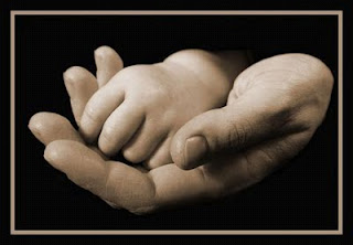 baby hand held in an adult hand against a black background
