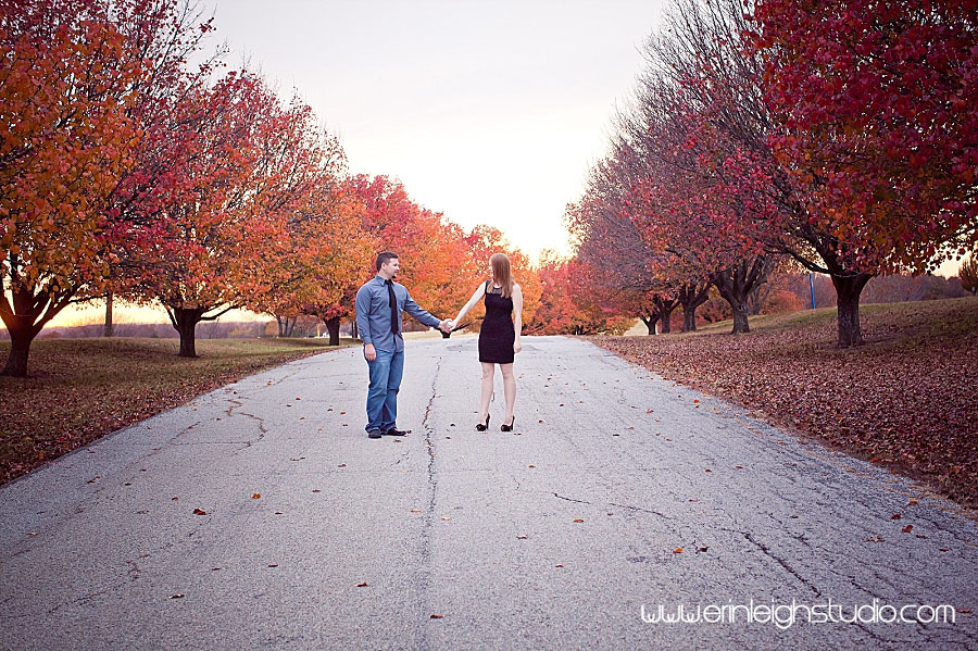 couple holding hands at park with fall trees