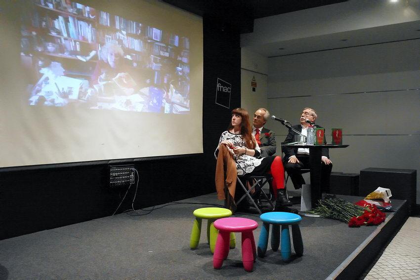 Foto da mesa de apresentação com um écrã por detrás onde se vê a imagem da autora o livro a discursar