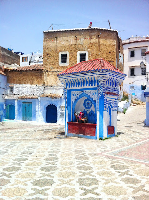 blue and white buildings in a city square in Morocco. One of the building has beautiful tiling.