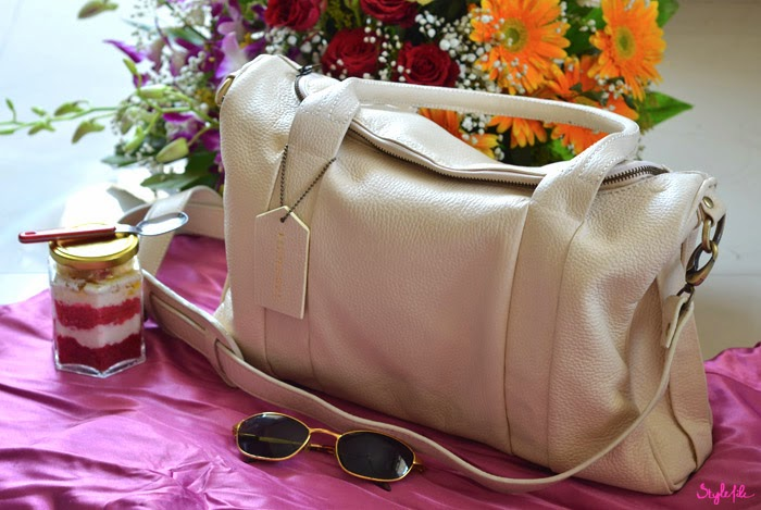 Summer picnic with a bouquet of african daisy flowers, a red velvet layered cake jar, Rayban sunglasses and Studio Pinwheel beige pebbled duffel handbag