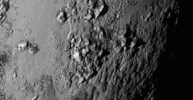 This close-up image of a region near Pluto's equator captured by New Horizons on July 14 reveals a range of youthful mountains rising as high as 11,000 feet (3.4 kilometers) above the surface of the dwarf planet. This iconic image of the mountains, informally named Norgay Montes (Norgay Mountains) was captured about 1 ½ hours before New Horizons' closest approach to Pluto, when the craft was 47,800 miles (77,000 kilometers) from the surface of the icy body. The image easily resolves structures smaller than a mile across. The highest resolution images of Pluto are still to come, with an intense data downlink phase commencing on Sept. 5. (Credit: NASA/Johns Hopkins University Applied Physics Laboratory/Southwest Research Institute)