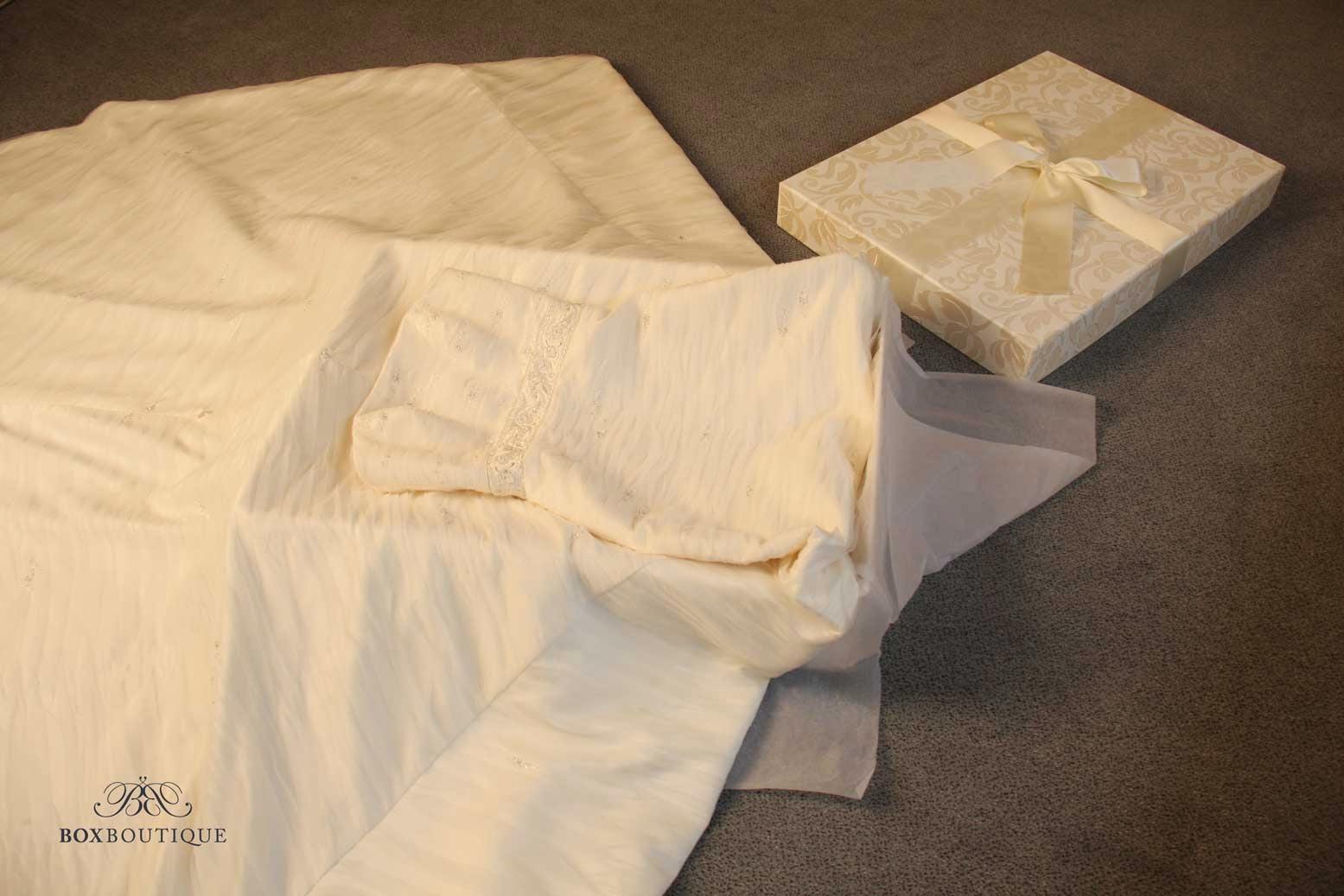 Legen Sie das Hochzeitskleid so über die Box, dass die Korsage beim Einschlagen noch hinein passt.