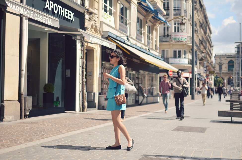 full shot of theserialshopper wearind a sixties inspired turquoise dress, with black flats, a croco bag and hm sunnies