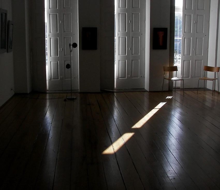 Vista sobre uma sala com portadas entreabertas, nas janelas, ao fundo, e um raio de luz oblíquo projectado no soalho