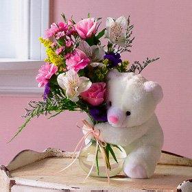 white teddy holding small vase of flowers