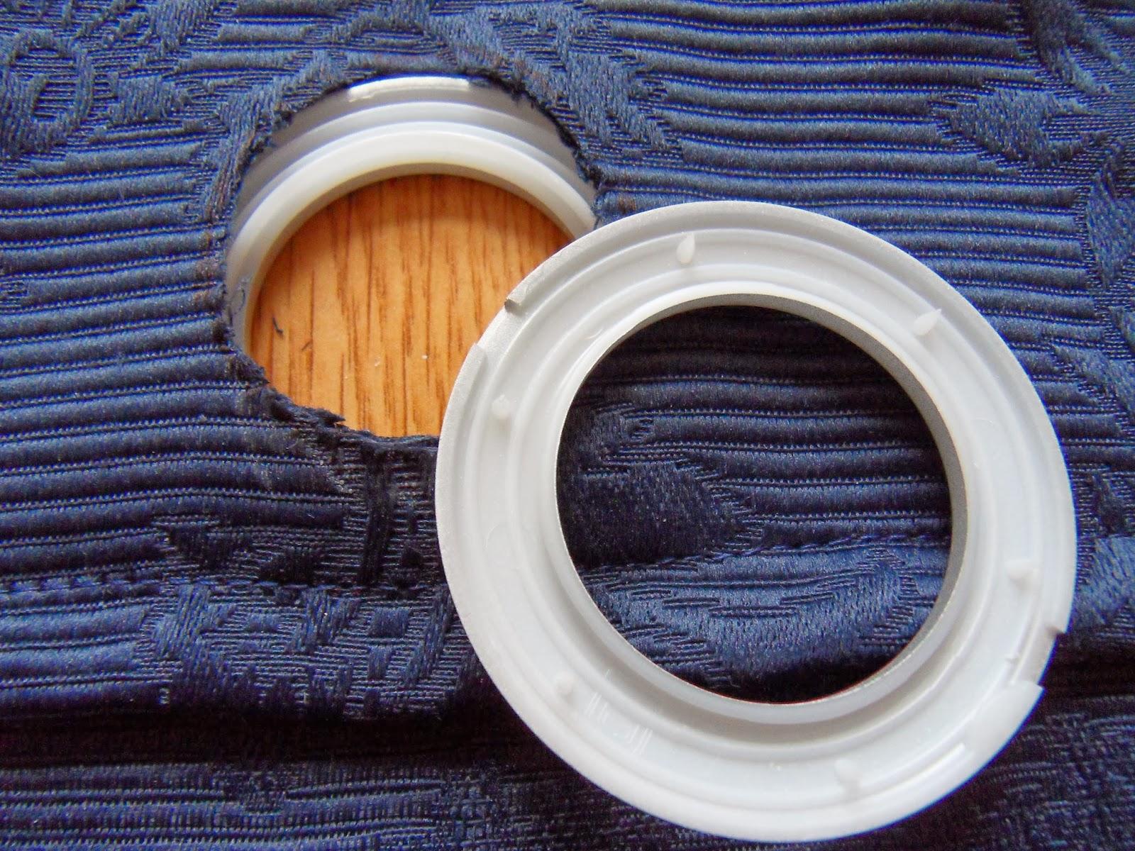 de ringen klik je dan om het gat heen en kant van de ringen heeft pinnetjes die zich in de stof vastzetten