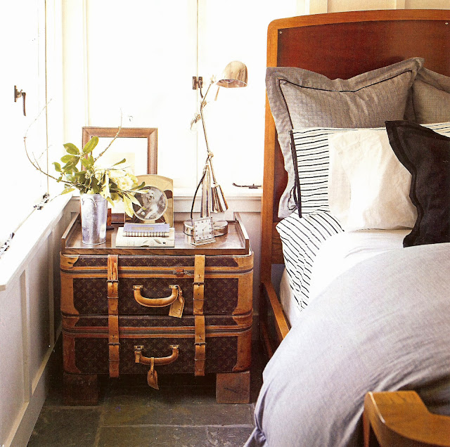 Bedroom with two Louis Vuitton trunks doubling as a nightstand