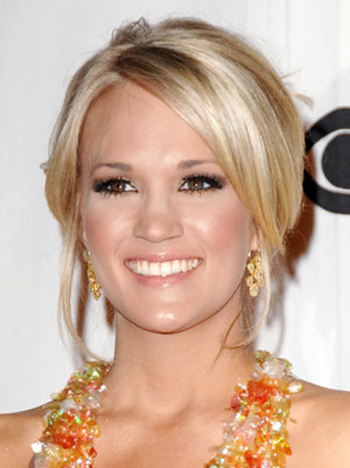 Smooth, loose pieces in front add balance to Carrie Underwood's twisted up hairstyle.