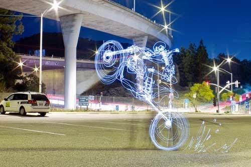 Fotografia de uma rua no início da noite. No canto, um viaduto, um carro. No centro da foto foi desenhado uma caveira empinando uma moto, mas este desenho foi feito com luz. ele é transparente na imagem, só aparece os contornos da moto e da caveira.