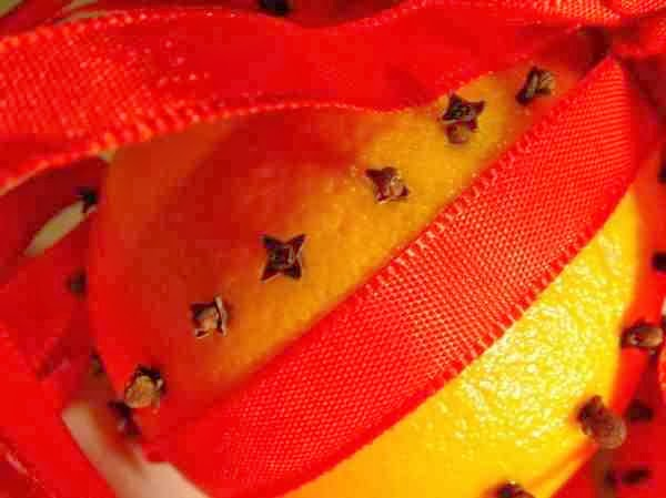 Pomarańcza udekorowana goździkami i wstążką