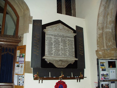 A white painted church wall, with a small window placed very high up.  The memorial tablet is decorated top and bottom with carving and there are four columns of names upon it.  On either side are dark slate strips with gold painted names for the 1939-45 war.  A shelf below carries candles and poppies.
