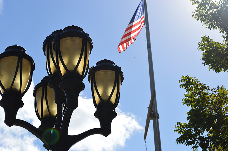 american flag and light post on a sunny day in the park