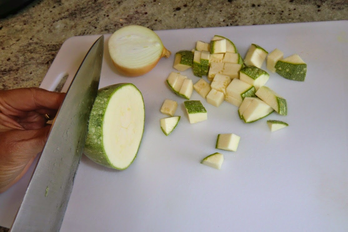 Slicing and dicing the courgettes and onions into small cubes