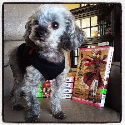 Murchie stands on a chair beside a stack of hardcover copies of A Bride's Story. He wears his black tank top. One of the manga is set upright to display the cover art, which features a woman in black-and-red central Asian dress with her arms spread wide and one foot crossed before the other as though she's dancing.