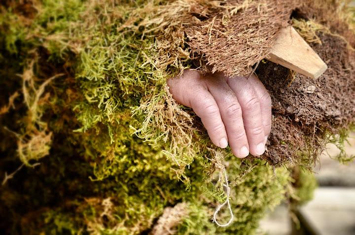 vista parcial de una mano de una de las mujers vestidas con musgo
