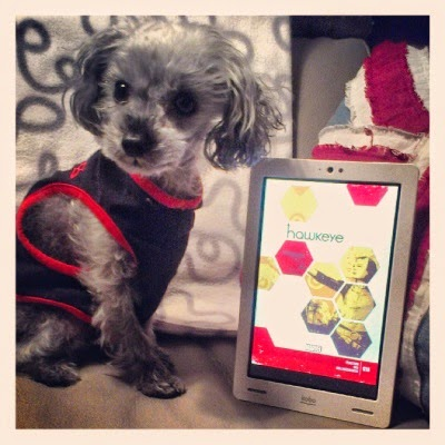 A fuzzy grey poodle, Murchie, sits beside a white Kobo with the cover art of Hawkeye 18 on its screen