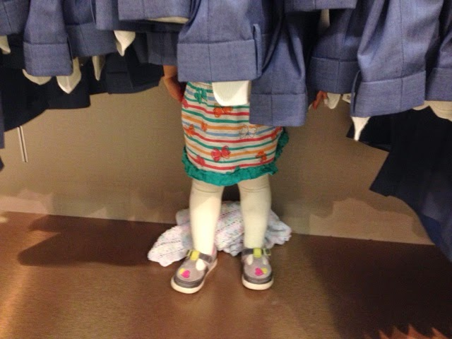 Tin Box Tot's legs poking out the bottom of a suit rack