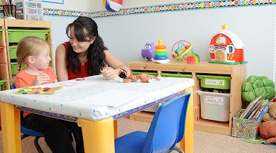 image of a young girl sitting with a teacher as they work on an arts and craft project together.