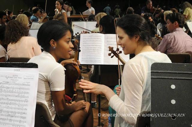 Una estudiante (I) de la Orquesta Juvenil del Conservatorio Amadeo Roldan conversa con una integrante (D) de la Orquesta Sinfónica de Minnesota,  durante el ensayo realizado en el Teatro Nacional de Cuba, en La Habana, el 15 de mayo de 2015.