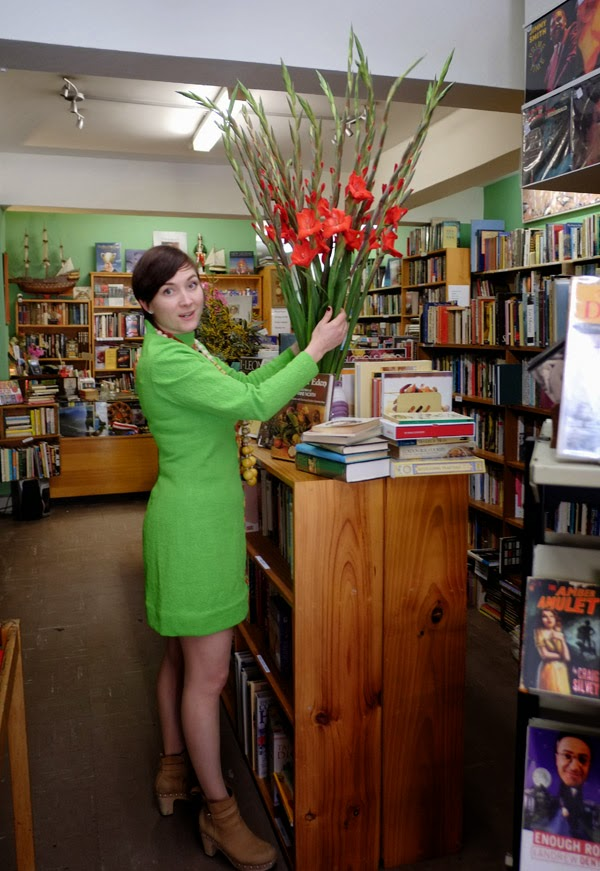 Tamara arranging Gladioli flowers in the shop wearing her lime green dress - Grand Days Bookshop Kings Cross, Woolloomooloo.