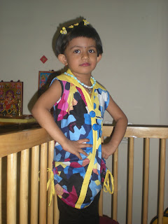baby girl wear multi color dress and yellow hair clip